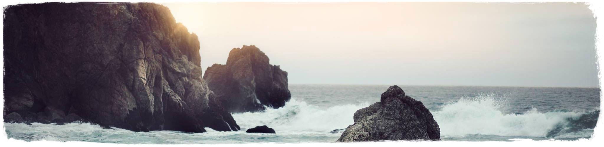 Ocean waves crashing on large rocks